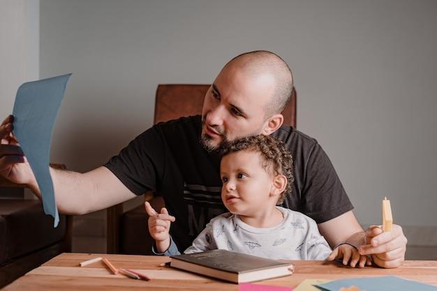 Papa et fils examinant une feuille avec des images peintes. apprendre à la maison