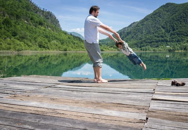 Papa et fils jouant sur le lac de montagne