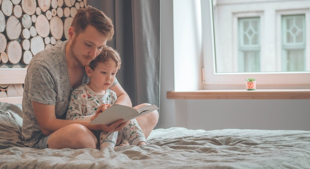 Papa et fils lisent un livre ensemble, souriant et se serrant dans leurs bras