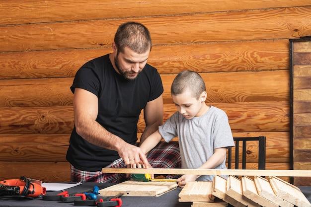 Papa et fils mesurent avec du ruban adhésif en bois, planifiant la construction d'une maison d'oiseaux