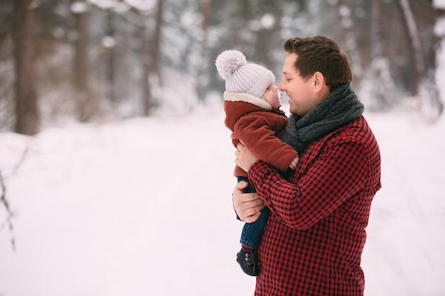 Papa heureux avec bébé fils tout en s'amusant dans la forêt d'hiver