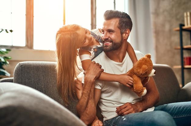 Papa heureux avec sa jolie fille et son ours en peluche câlin et amusez-vous assis sur le canapé du salon à la maison. joyeuse fête des pères.