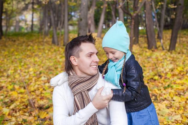 Papa heureux et sa petite fille s'amusant dans le parc par une journée ensoleillée d'automne