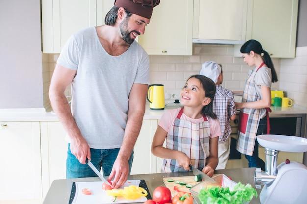 Papa heureux se tient avec sa fille et coupe les légumes. ils se regardent et sourient. maman travaille avec son fils derrière eux au poêle.