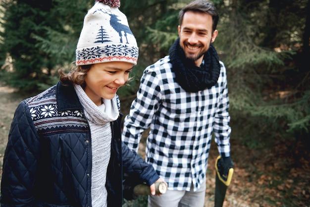 Papa heureux et son fils portant l'arbre de noël