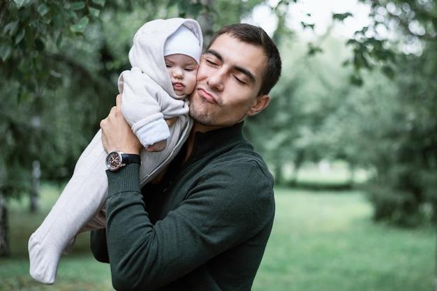 Papa homme aux cheveux noirs en veste verte avec bébé dans ses mains dans le parc, concept de paternité