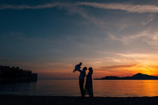 Papa jetant un petit enfant maman et papa se tiennent sur la plage sur fond de coucher de soleil