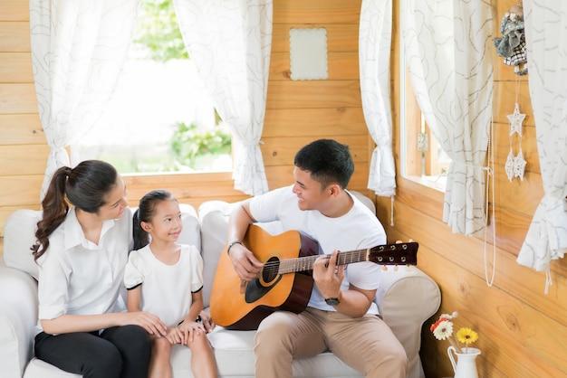 Papa joue de la guitare pour une famille. et chantant joyeusement dans la maison.