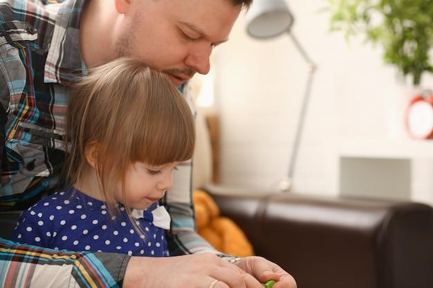 Papa joue avec une jolie petite fille en robe bleue