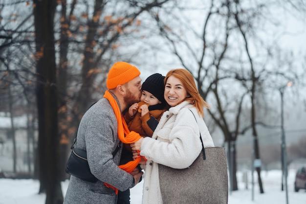 Papa maman et bébé dans le parc en hiver