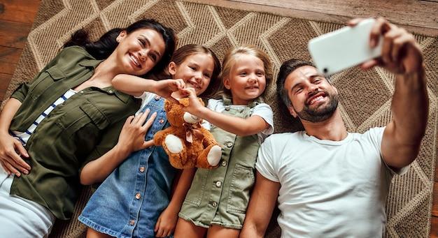 Papa, maman et deux jolies filles s'allongent sur le tapis par terre dans le salon et prennent un selfie sur un smartphone. une famille heureuse s'amuse ensemble.