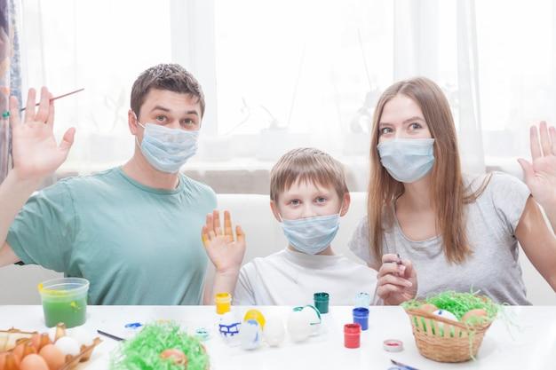 Papa, maman et enfant à table avec des masques médicaux peignent des oeufs de pâques pour les vacances