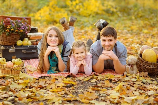 Papa, maman et fille s'amusent ensemble lors d'un pique-nique d'automne dans la rue.