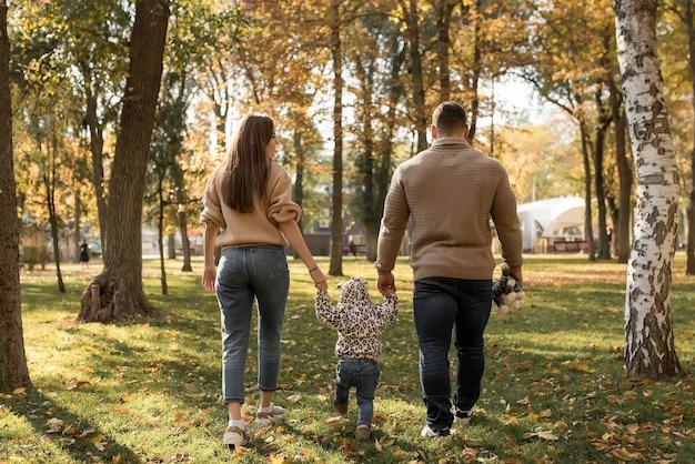Papa et maman tiennent la main de leur fille dans la forêt d'automne
