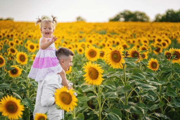 Papa marche avec sa fille sur un champ avec un tournesol. l'enfant a une drôle d'expression faciale