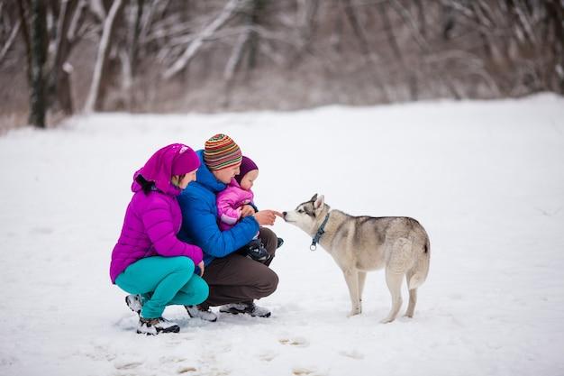 Le papa montrant à son adorable petite fille une chute de neige, jour de neige d'hiver
