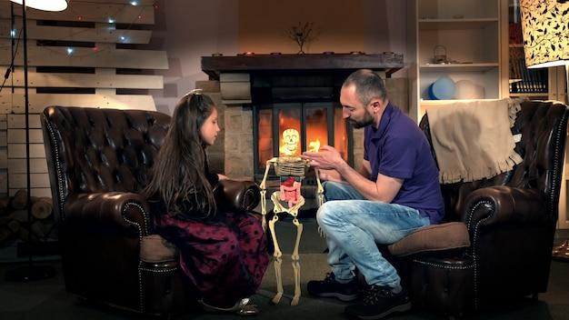 Papa parle à sa fille de la fonction des côtes dans le squelette humain