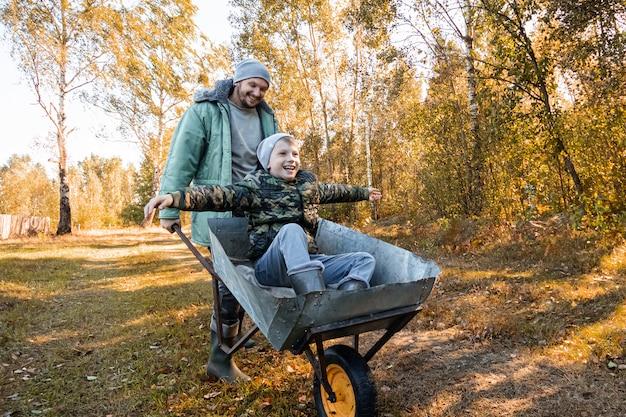 Papa passe du temps avec son fils, un petit garçon heureux poussé par un papa