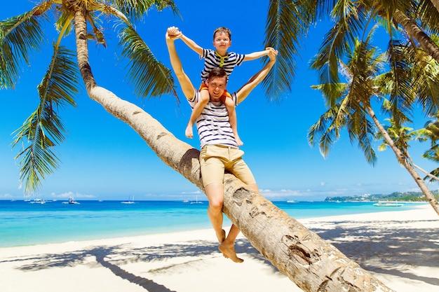 Papa et petit fils s'amusent sur un cocotier sur une plage tropicale de sable. le concept de voyage et de vacances en famille.