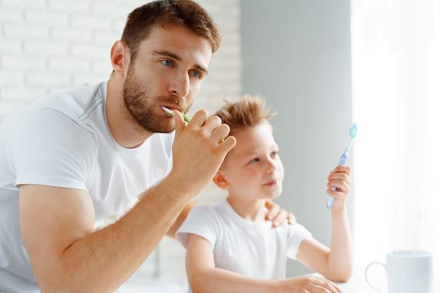 Papa et petit fils se brosser les dents ensemble dans la salle de bain