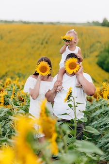 Papa porte une petite fille sur ses épaules dans le domaine des fleurs. le concept de vacances d'été. fête des pères, des mères et des bébés. passer du temps ensemble. mise au point sélective
