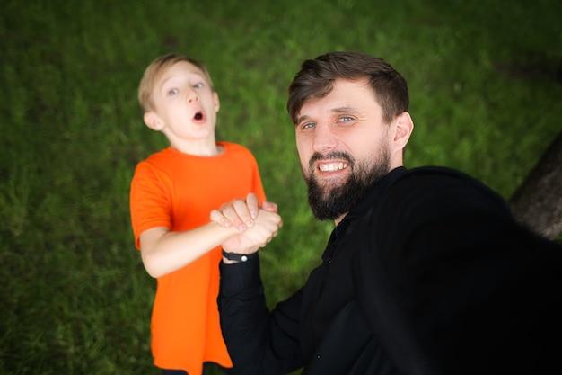 Papa prend un selfie tenant la main de l'enfant