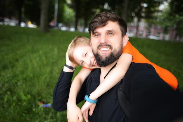 Papa regarde la caméra et prend un selfie, l'enfant le serre dans ses bras par le cou et rit joyeusement