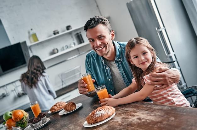 Papa et sa belle petite fille prennent le petit déjeuner dans la cuisine et discutent. maman se prépare à manger en arrière-plan. notion de famille heureuse.