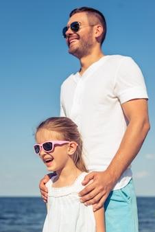 Papa et sa fille dans la mer en arrière-plan.