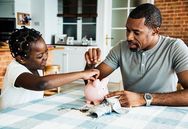 Papa et sa fille économisent de l'argent à la tirelire