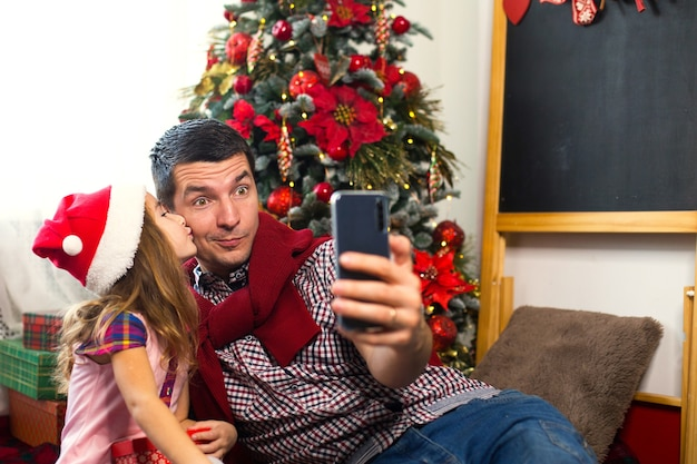 Papa et sa fille près de l'arbre de noël avec un smartphone prennent un selfie, communiquent via une connexion vidéo. salutations de noël, une boîte-cadeau, une fille dans un bonnet de noel agitant bonjour. nouvel an, décor de vacances