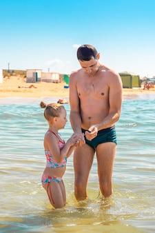 Papa et sa fille regardent une petite méduse dans leur main. nager dans la mer. vacances d'été sur la côte.