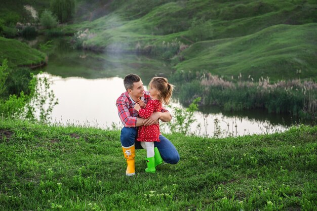 Papa avec sa petite fille dans des bottes en caoutchouc de couleur vive lors d'une promenade au bord du lac le jour des papas