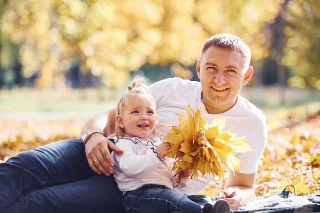 Papa avec sa petite fille se repose dans un magnifique parc d'automne aux beaux jours.