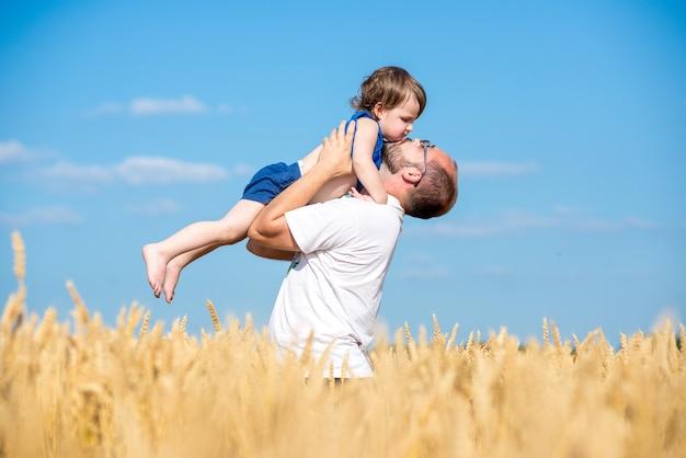 Papa Avec Son Fils Dans Un Champ De Blé. Père Et Fils S'amusant En Plein Air Dans Un Champ De Blé Photo Premium
