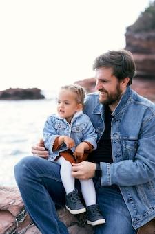 Papa souriant avec une petite fille dans ses bras est assis sur un rivage rocheux sur fond de montagnes