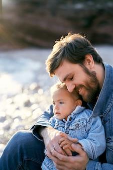 Papa souriant s'assoit et embrasse une petite fille sur un gros plan de plage de galets