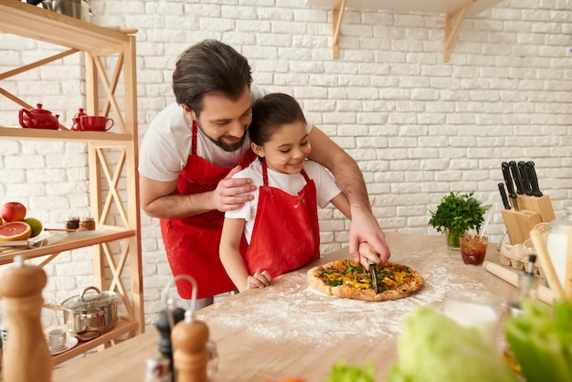 Papa souriant avec sa fille coupant une pizza à la maison.