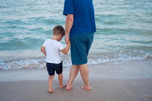 Papa tient la main de son fils. père enfant passer du temps ensemble vacances à la mer jeune homme petit garçon marchant sur la plage fête des pères. famille avec un enfant. bonne enfance avec papa.