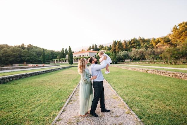 Papa tient sa petite fille dans ses bras debout sur le chemin dans le parc près de la villa milocer maman est