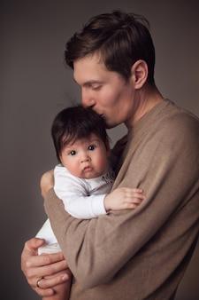 Papa tient son petit fils dans ses bras et lui embrasse la tête