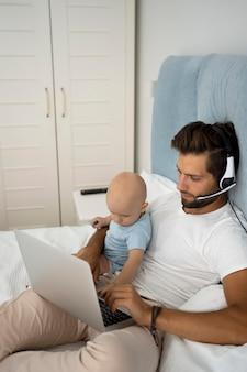 Papa travaillant à domicile pendant la quarantaine avec enfant