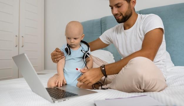 Papa travaillant sur un ordinateur portable à la maison pendant la quarantaine avec enfant