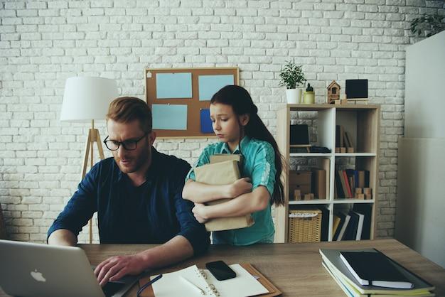 Papa travaille à l'ordinateur et une fille contrariée se tient à proximité.