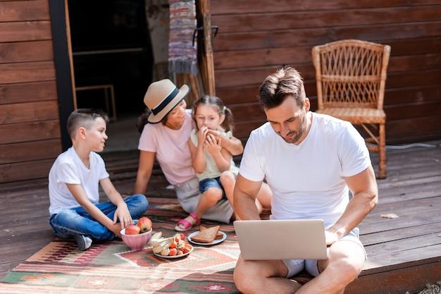 Papa travaille en vacances en famille, utilise un ordinateur portable assis sur le porche d'une maison de campagne en bois, en arrière-plan sa femme et ses deux enfants