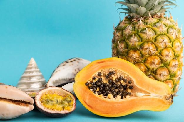 Papaye coupée mûre, ananas, fruit de la passion, coquillages sur fond bleu. vue latérale, copiez l'espace.