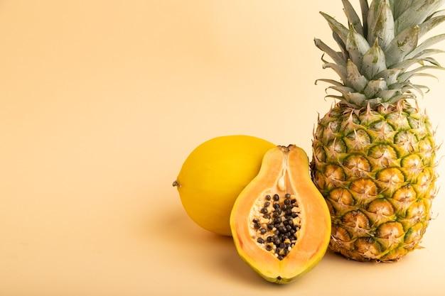 Papaye coupée mûre, ananas, melon, sur fond pastel orange. vue latérale, copiez l'espace. tropical,