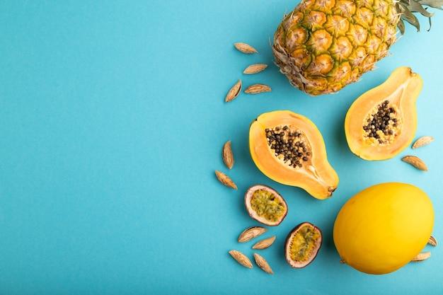 Papaye coupée mûre, ananas, melon, fruit de la passion, amandes sur fond bleu pastel. vue de dessus,