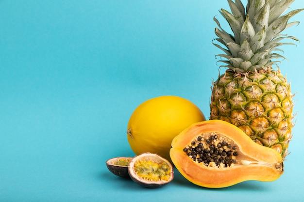 Papaye coupée mûre, ananas, melon, fruit de la passion, sur fond bleu pastel. vue latérale, copiez l'espace.