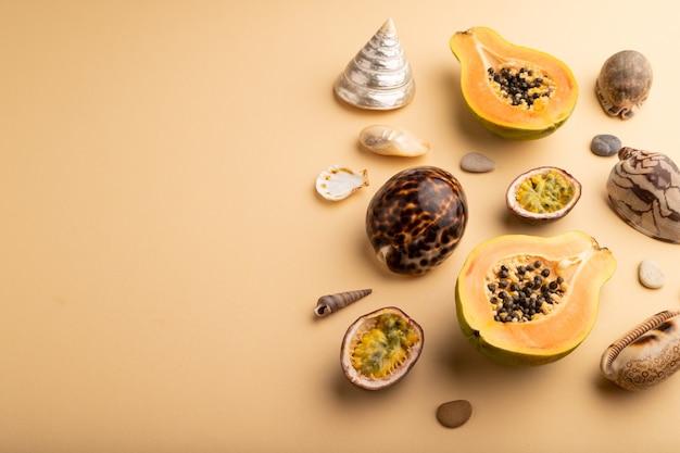 Papaye coupée mûre, fruit de la passion, coquillages, cailloux sur fond orange. vue latérale, copiez l'espace.